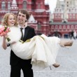 Stock Photo: Groom holding young beautiful bride in his arms