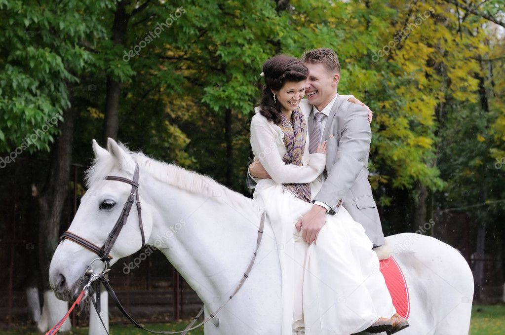 Happy bride and groom on a horse — Zdjęcie stockowe #10261472