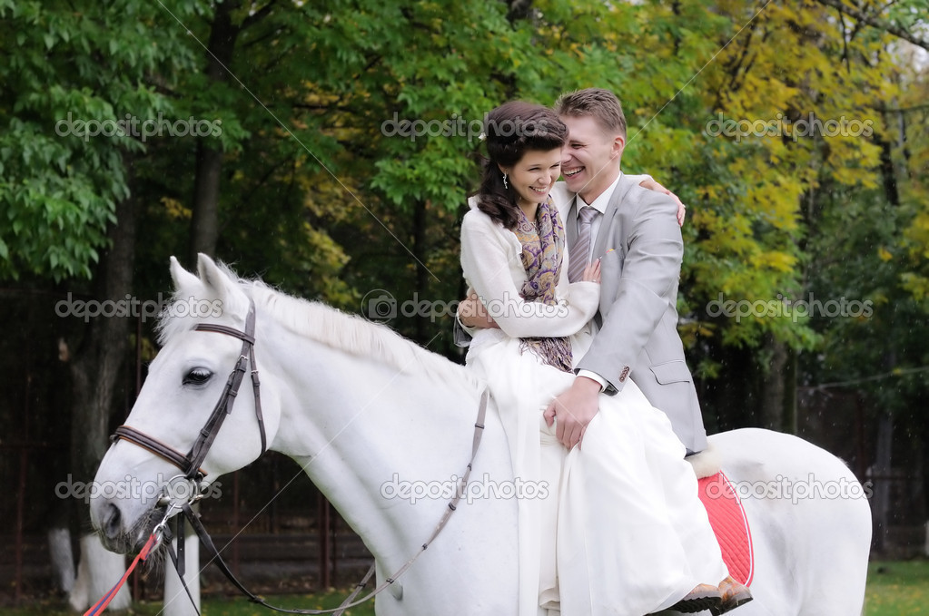 Happy bride and groom on a horse — Stockfoto #10261472