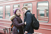 Happy young couple on railway station platform — Stock Photo