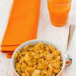 Cornflakes in the bowl with spoon and juice - Stock Photo