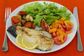 Fried fish with vegetables and salad — Stock Photo