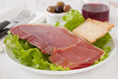 Prosciutto with toasts and glass of red wine — Stock Photo