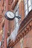 Old clock and Icicles on a brick wal — Stock Photo