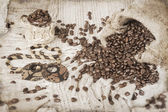 Ceramic cup of coffee, roasted coffee beans and wooden bijouteri — Stock Photo