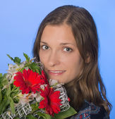 Young happy woman with flowers on blue background — Stock Photo