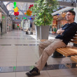 Portrait of young man on bench in mall — Stock Photo #8370595