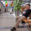 Portrait of young man on bench in mall — Stock Photo