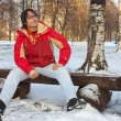 Young man sitting on bench in winter park — Stock Photo