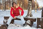Joven sentado en el banco en el parque de invierno — Foto de Stock