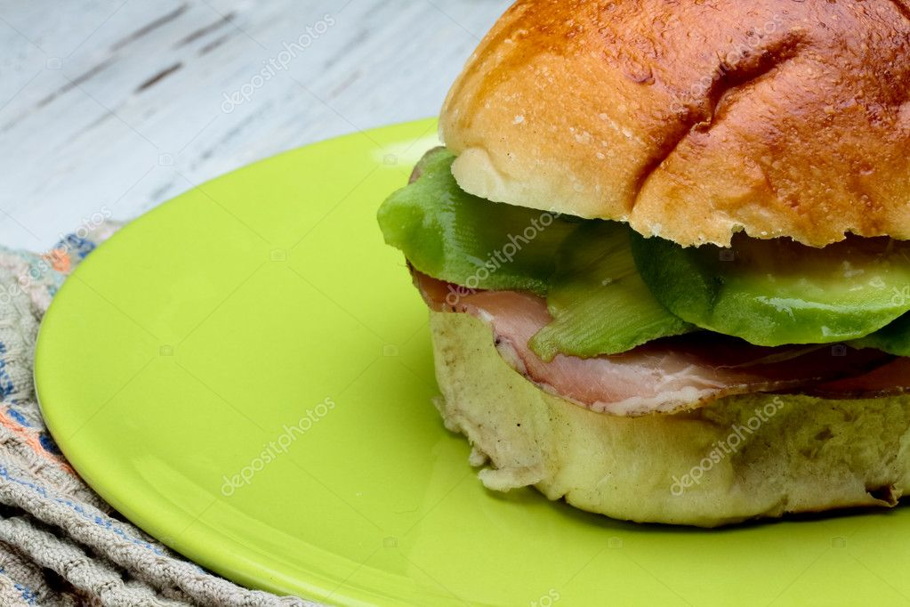 Brioche with avocado and loin of pork — Stock Photo #10456354