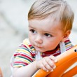 Young toddler   on a swing in the playground. — Stock Photo