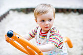 Year old boy swinging on a swing in the park on the playground — Stock Photo