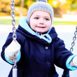 Cute baby boy   on swing in autumn park — Stock Photo