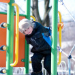Boy playing  on the playground  in winter park. — Stock Photo