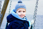 Little boy playing on a swing. Winter — Stock Photo
