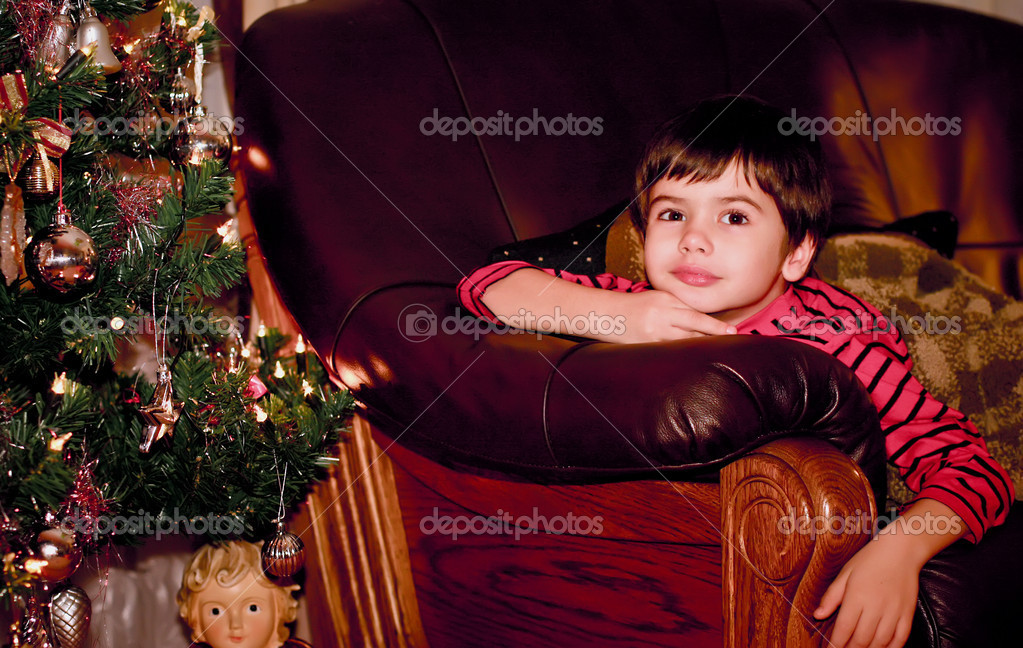 Portrait of an attractive boy near a Christmas tree at night. New Year. Wait for Santa Claus. Christmas. — Stock Photo #8389907