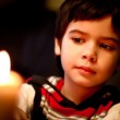 Beautiful boy looks at a candle flame at night — Stock Photo