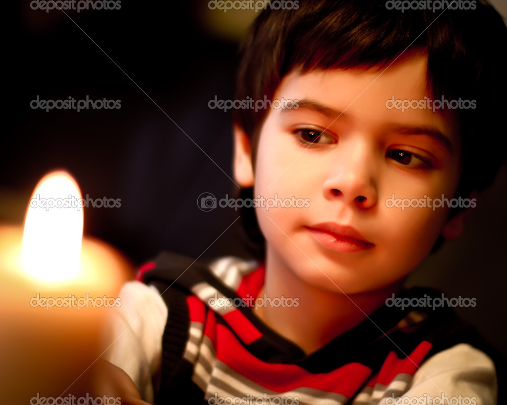 Beautiful boy looks at a candle flame at night — Stock Photo #8462384