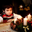 Cute boy sitting at a table in front of a Christmas wreath and candles. — Stock Photo