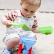 A little boy in the sandbox - Stock Photo
