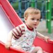 Cute little boy  come down from the children`s slide - Stock Photo