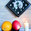 Stock Photo: Kitchen still-life with orange and apple against black hours