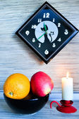 Kitchen still-life with an orange and an apple against black hours — Stock Photo
