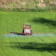 Farm tractor spraying field before planting — Stock Photo #9779988