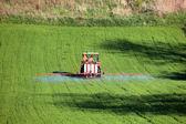 Farm tractor spraying field before planting — Stok fotoğraf