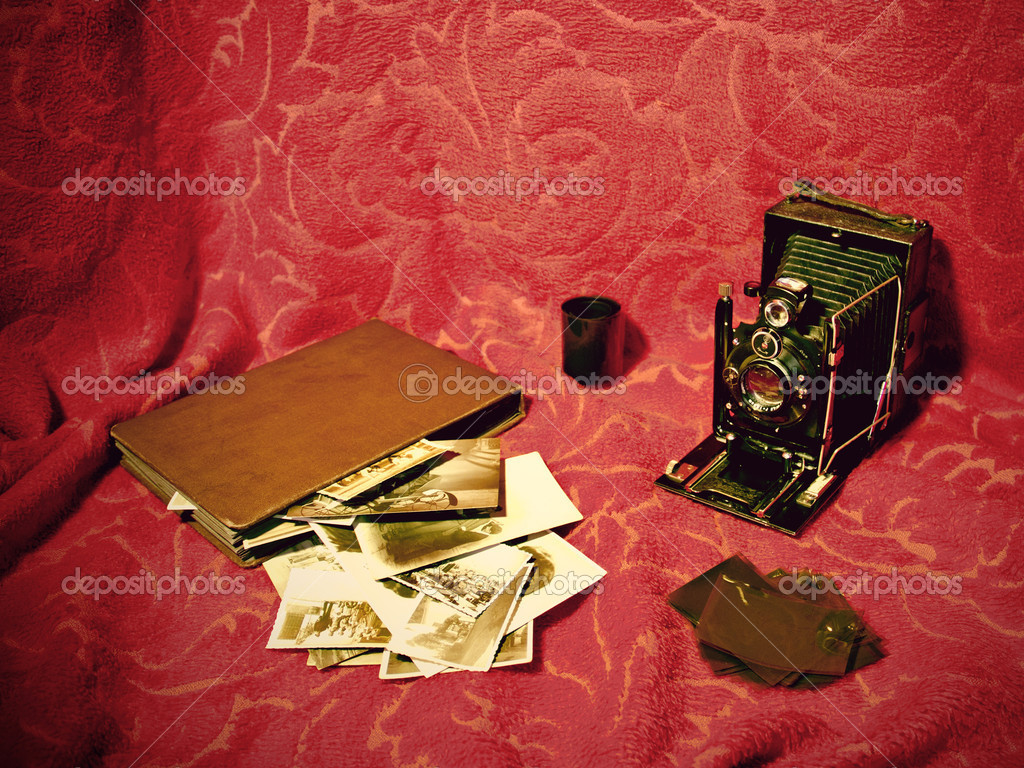 A very old camera set with old album and photographs and some film over a retro background.  Stock Photo #8598567
