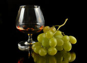 Glass of brandy and grapes — Stock Photo