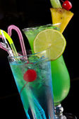 Green cocktail with pineapple and blue cocktail with ice and lim — Stock Photo