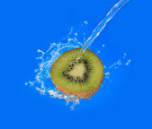 Water splash on kiwi half on blue background — Stok fotoğraf