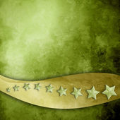 Green background with gold ribbon strip and stars — Stok fotoğraf