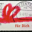 Royalty-Free Stock Photo: GERMANY - CIRCA 2001: A stamp printed in Germany shows drawing of a red ribbon with the words for you, circa 2001