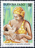 BURKINA FASO - CIRCA 1985: A stamp printed in Burkina Faso dedicated to combating child mortality, shows a mother breastfeeding her child, circa 1985 — Stock Photo