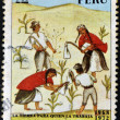 PERU - CIRCA 1972: A stamp printed in Peru shows Indians working the land with the message: the land to the tiller, circa 1972 - Stock Photo