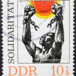 Stock Photo: GERMANY (GDR) - CIRC1981: stamp printed in Germany dedicated to international solidarity, shows black mbreaking chains of slavery, circ1981