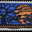 Stock Photo: USA - CIRCA 1974: The Legend of Sleepy Hollow stamp is issued in time for Halloween. The scene shows a headless horseman chasing Ichabod in the light of a giant
