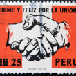 Foto Stock: PERU - CIRCA 1980: A stamp printed in 1980 shows holding hands on the flag of peru, strong and happy by the union, circa 1980