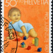 SWITZERLAND - CIRCA 1987: A stamp printed in Switzerland shows child playing with wooden figures, circa 1987 - ストック写真