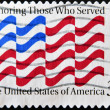 UNITED STATES OF AMERICA - CIRCA 1999: A stamp printed in USA shows the flag, dedicated to honoring those who served, circa 1999 - ストック写真