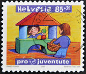 SWITZERLAND - CIRCA 2003: A stamp printed in Switzerland shows two children playing to sell fruit, circa 2003 — Stock Photo