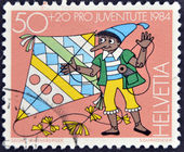 SWITZERLAND - CIRCA 1984: A stamp printed in Switzerland shows Pinocchio with a kite, circa 1984 — Stock Photo