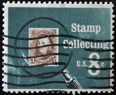 UNITED STATES OF AMERICA - CIRCA 1972: A stamp printed in USA shows Pictures magnifying glass over United States postage stamp, circa 1972 — Stock Photo