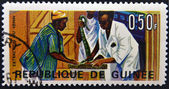 GUINEA - CIRCA 1967: A stamp printed in Guinea shows Extraction of snake venom, circa 1967 — Stock Photo