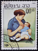 LAOS- CIRCA 1985: A stamp printed in India shows woman breast-feeds the baby, circa 1985 — Stock fotografie