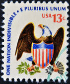 "USA - CIRCA 1975: A stamp printed in USA from the ""Americana"" issue showing an eagle and shield and the inscription ""One Nation Indivisible-E Pluribus Unum"", circa 1975. — Stock Photo"