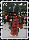 MALTA - CIRCA 2006: A stamp printed in Malta shows penitents carrying the cross at Easter, circa 2006 — Stock Photo